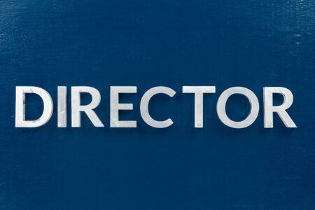 the word director laid with silver metal letters on classic blue painted board background.