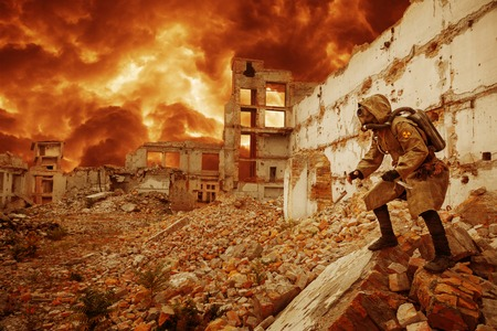 Post apocalypse. Sole survivor in tatters and gas mask on the ruins of the destroyed city