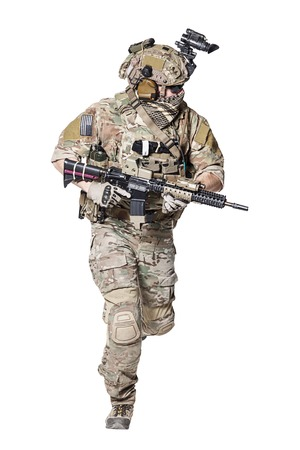 Elite member of US Army rangers in combat uniforms with his shirt sleeves rolled up, in helmet, eyewear and night vision goggles, running in action turning around. Studio shot, white background
