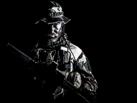 Bearded Special forces United States in Camouflage Uniforms studio shot half length black background. Holding weapons, wearing jungle hat, Shemagh scarf, he is ready to kill. Backlit