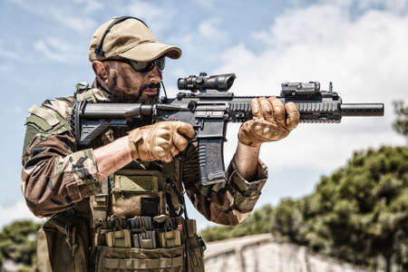 Photo pour Private military company mercenary, brutal looking special forces fighter in battle uniform and plate carrier, wearing radio headset and sunglasses, holding service rifle in hands, ready to fight - image libre de droit