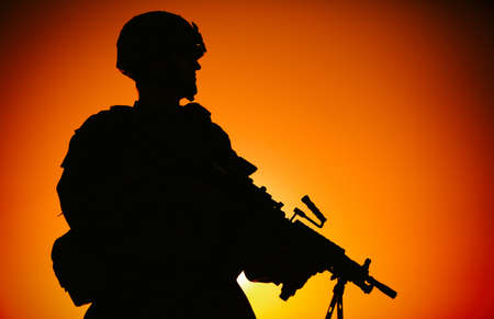 Photo pour Silhouette of army infantry soldier, commando in combat helmet, armed light machine gun, standing on background of ocean horizon and sunset. Marine Corps rifleman, special forces shooter on sea shore - image libre de droit
