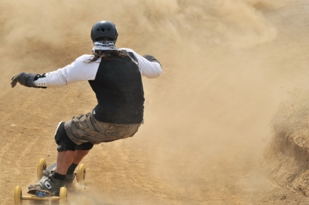 Rear view at mountain boarder riding down through dust