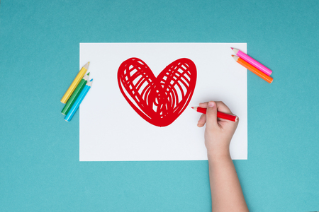 a little boy draws a heart on a white sheet