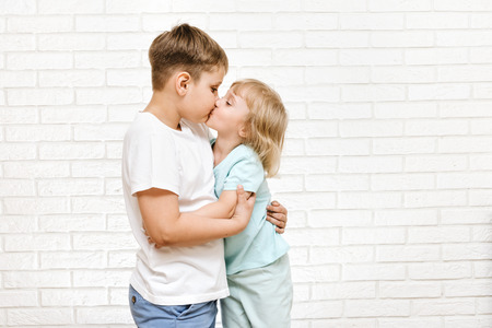 Foto de boy and girl are kissing against the background of a white brick wall - Imagen libre de derechos