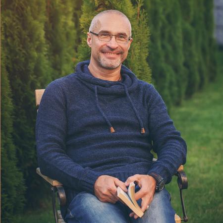 Photo pour The mature senior man reading novel in country home garden, toning image - image libre de droit