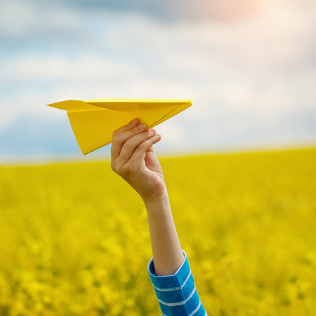 Photo pour Paper airplane in children hands on yellow background and blue sky in coudy day - image libre de droit