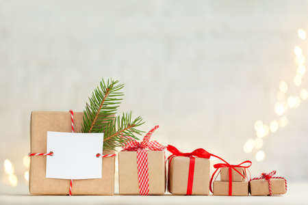 Photo pour Christmas handmade gift box decorated with evergreen branch and empty blank gift card and different Christmas gift boxes with red ribbon. - image libre de droit