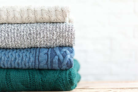 Photo pour Stack folded of cozy knitted sweaters on white and wooden background - image libre de droit
