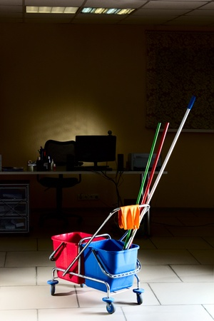 Photo pour Trolley with water backets and cleaning stuff in the middle of the empty office - image libre de droit