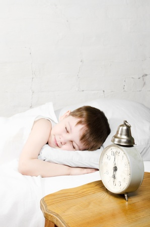 Small toddler boy (4 years) is sleeping in bed. Brick wall at the background. Old clock show 6 o'clock.