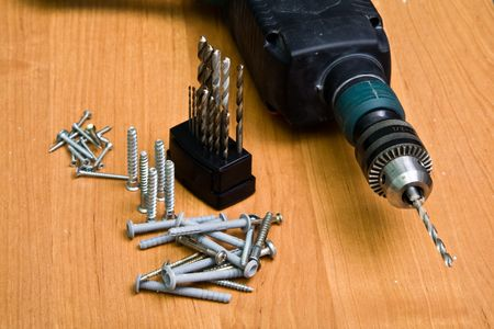 Photo of a drill, bit set and screws