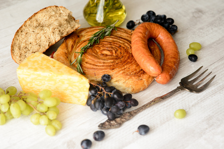 sausage,cheese,bread,grapes on a wooden Board with olive oil in the bottleの写真素材
