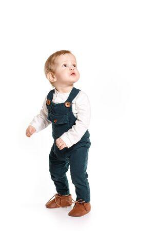 Foto de A one-year-old boy in a green jumpsuit on a white background - Imagen libre de derechos