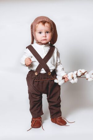 A cute stylish one year old boy in a white linen shirt and brown trousers looks thoughtfully into the frame