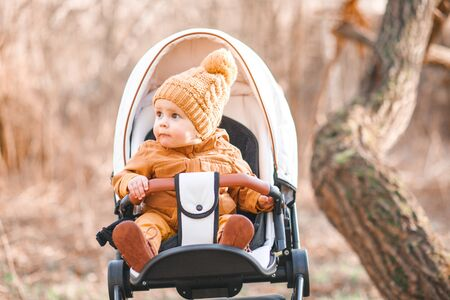 Photo for Cute little beautiful one year old boy sitting in a stroller and waiting for his mother - Royalty Free Image