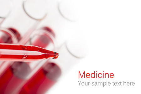 Pipette with drop of blood and test tubes