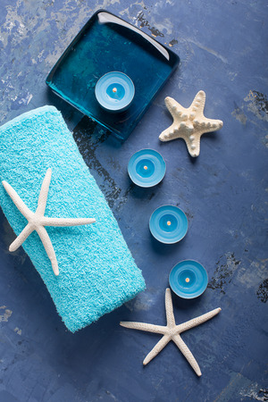 SPA still life with towel, candles and starfish on blue surface