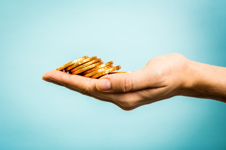 Hand holding golden coins concept on blue background.