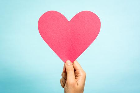 Photo pour Hand holding red paper love heart shape on blue background.  - image libre de droit