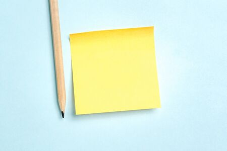 Yellow blank empty paper message with a pencil on blue background. Negative space.