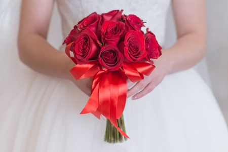 Bright red bouquet of roses in the hands of a girl close-up