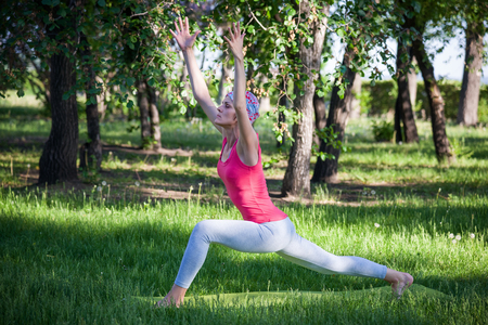 Yoga in the Park, outdoors , womens health, Yoga woman. The concept of healthy lifestyle and recreation. flexible young woman practicing yoga and gymnastics in the Park.