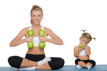 Foto de Mom and daughter engage in fitness dumbbells of green apples - Imagen libre de derechos