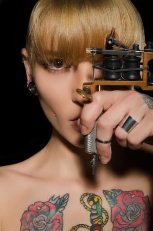 tattooed beautiful woman with tattoo machine, dark background