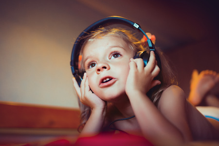 Photo pour Cute little kid listening music lying on bed at home - image libre de droit
