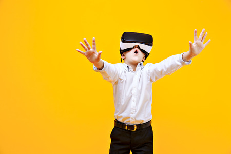 Photo pour Kid in formal outfit wearing VR glasses putting hands out in excitement isolated on orange background. - image libre de droit