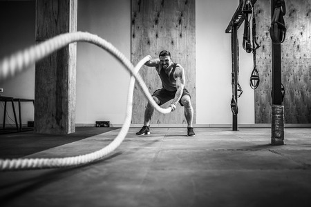 Foto de Men with rope in functional training fitness gym - Imagen libre de derechos