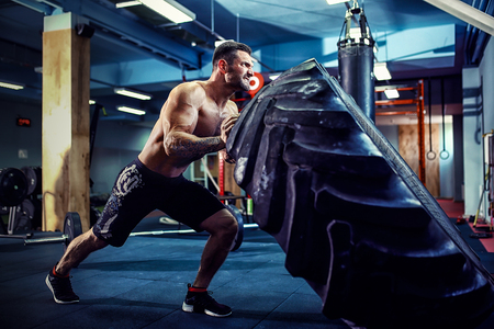 Photo for Shirtless man flipping heavy tire at crossfit gym - Royalty Free Image