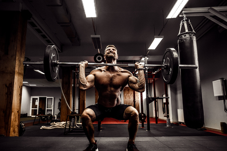 Foto de Muscular fitness man doing deadlift a barbell over his head in modern fitness center. Functional training. Snatch exercise - Imagen libre de derechos