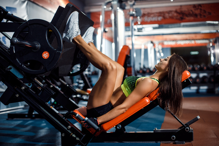 Foto de Woman doing fitness training on a leg extension push machine with weights in a gym - Imagen libre de derechos