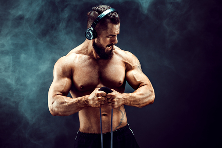 Foto de Fitness man in headphones exercising with stretching band in studio. Muscular sports man exercising with elastic rubber band. Fit, fitness, exercise, workout and healthy lifestyle - Imagen libre de derechos
