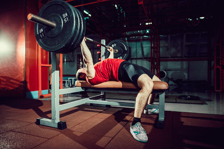 Foto de Very Strong man doing bench press workout in gym. - Imagen libre de derechos