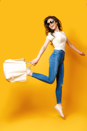 Photo pour Beautiful young woman in sunglasses, white shirt, blue jeans posing, jumping with bag on the yellow background - image libre de droit