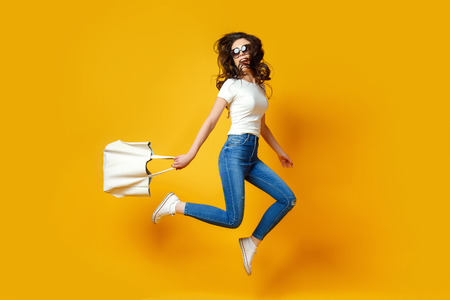 Foto de Beautiful young woman in sunglasses, white shirt, blue jeans posing, jumping with bag on the yellow background - Imagen libre de derechos