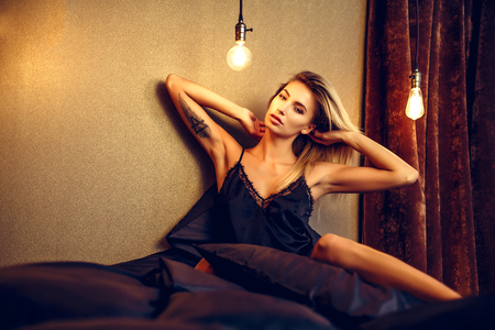Photo for fashion photo of sexy glamour woman with blonde hair wearing elegant lace lingerie, lying on black silk bed. - Royalty Free Image