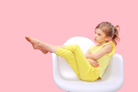 Photo pour Dreaming Stylish little girl in yellow clothes sitting and posing in chair on pink background. - image libre de droit