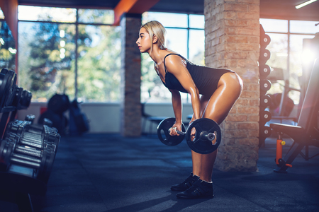 Sexy athletic girl working out in gym. Fitness woman doing exercise with barbell. Deadlift. Sexy beautiful butt