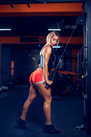 Foto de Sexy athletic girl working out in gym. Fitness woman doing exercise for triceps. Beautiful butt in legging - Imagen libre de derechos
