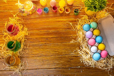 Photo for Background with colorful eggs in basket, paints, brushes. Wooden table decorating for holiday. Top view. - Royalty Free Image