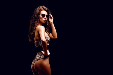 Photo pour Confident young fit curvy woman in sunglasses and leopard bodysuit posing on studio background. Animal print - image libre de droit