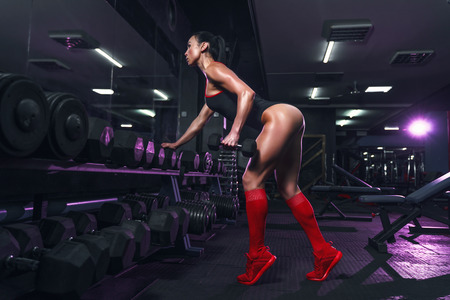 Foto de Attractive fit sexy woman in the gym crouches with a barbell. Woman training back. Colored smoke - Imagen libre de derechos