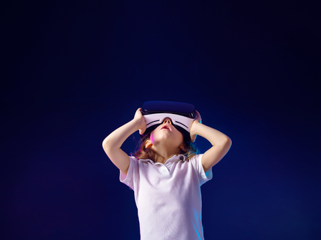 Foto de Girl 7 y.o. experiencing VR headset game on colorful background. Child using a gaming gadget for virtual reality. Futuristic goggles at young age. Virtual technology - Imagen libre de derechos
