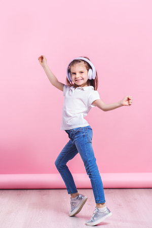 Photo for Girl listening to music in headphones an dance. Cute child enjoying happy dance music, smile, posing on pink studio background wall. - Royalty Free Image