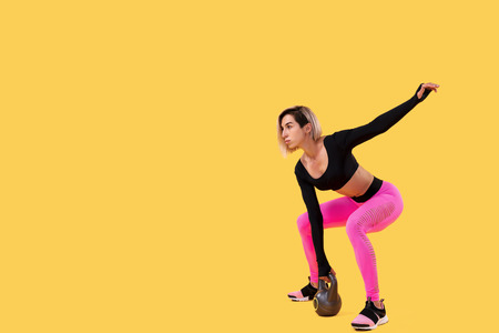 Photo for Fitness woman in fashionable pink and black sportswear work out with kettlebell on yellow background. Strength and motivation. - Royalty Free Image