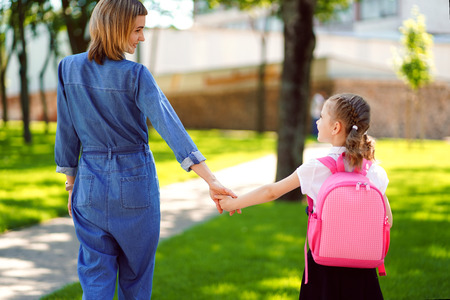 Photo pour Parent and pupil of primary school go hand in hand. Woman and girl with pink backpack behind the back. Beginning of lessons. First day of fall - image libre de droit